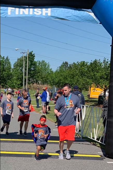 Man and child crossing finish line at Superheroes 5K